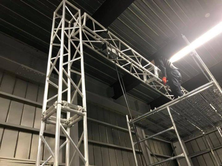 LEDビジョン用トラス組立その3 中央のローリングタワーに登った人が左右傾けて、片側づつウィンチで巻き上げます。